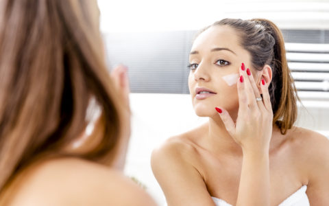 Woman looking in the mirror putting on sunscreen