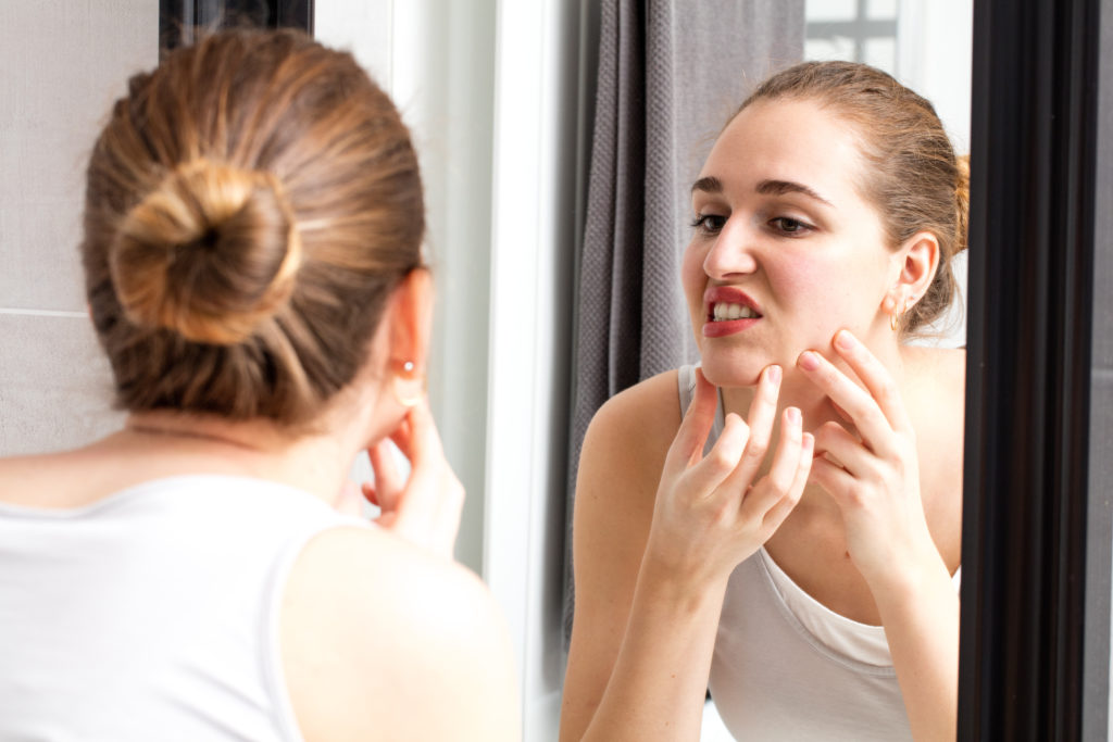 woman picking at her acne in the mirror