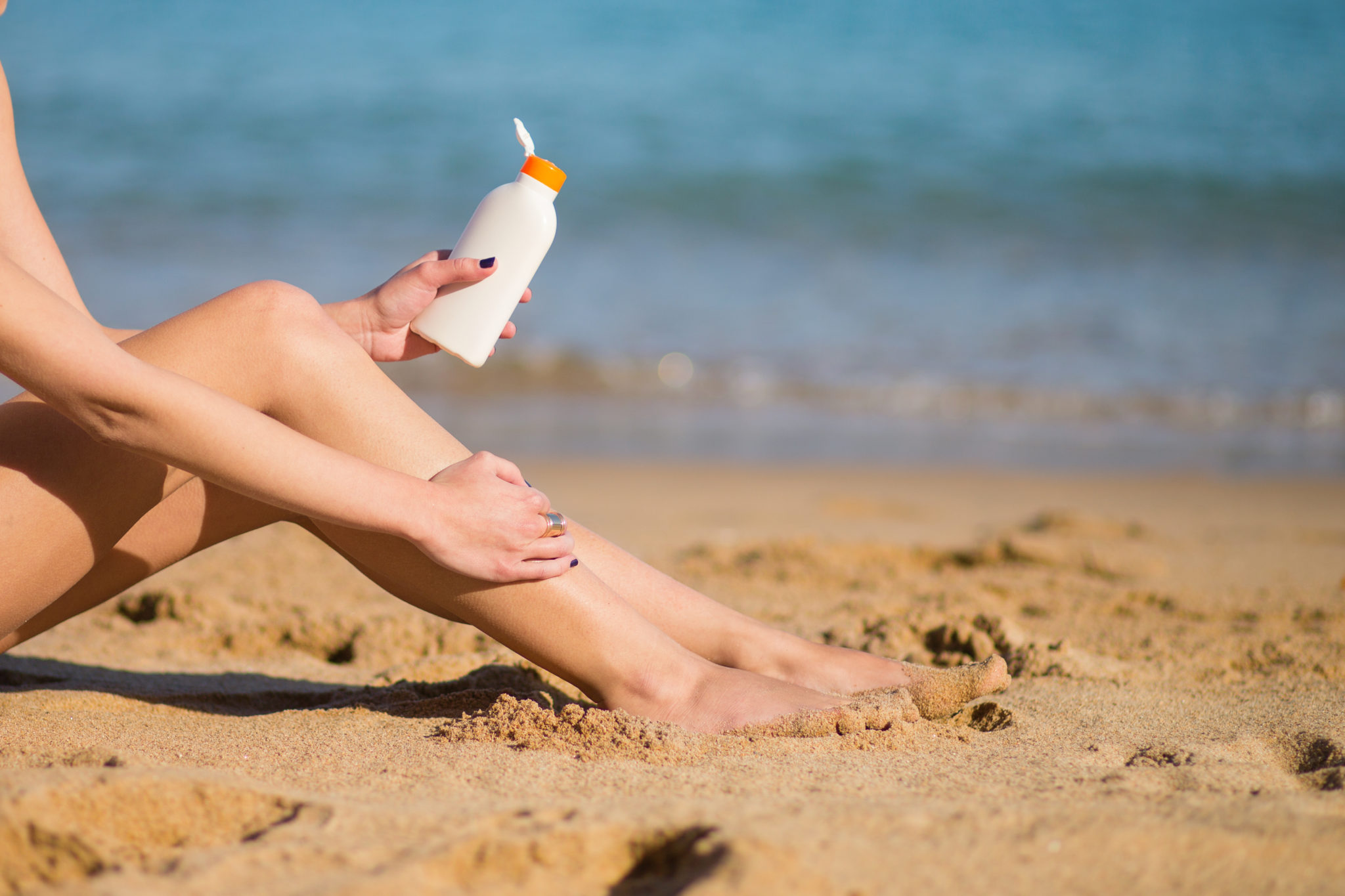 woman on the beach putting on sunscreen